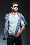 Η μόδα στούντιο πυροβόλησε: όμορφος νεαρός άνδρας που φορά τα τζιν, το πουκάμισο και τα γυαλιά ηλίου Στοκ Εικόνα