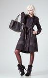 Η μόδα στούντιο πυροβόλησε: όμορφο κορίτσι στο μαύρες παλτό και τις μπότες, με την τσάντα διαθέσιμη Στοκ Εικόνες