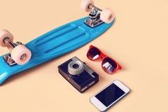 Η μόδα φαίνεται έννοια Μπλε skateboard, κόκκινα γυαλιά ηλίου, εκλεκτής ποιότητας κάμερα και smartphone οθόνης Στοκ φωτογραφία με δικαίωμα ελεύθερης χρήσης