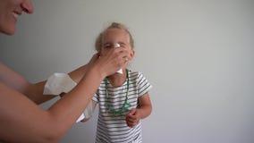 Η μύτη χτυπήματος μικρών κοριτσιών και παίρνει το μυξιάρες πρόσωπο Μητέρα που βοηθά το καθαρό πρόσωπο κορών απόθεμα βίντεο