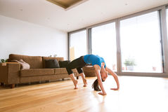 Η νέα άσκηση γυναικών στο σπίτι, τέντωμα, που κάνει τη γέφυρα θέτει Στοκ Εικόνες
