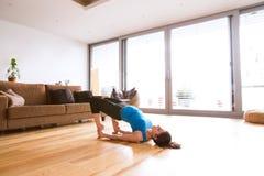 Η νέα άσκηση γυναικών στο σπίτι, τέντωμα, που κάνει τη γέφυρα θέτει Στοκ φωτογραφία με δικαίωμα ελεύθερης χρήσης