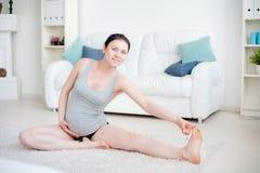 Η νέα έγκυος γυναίκα κάνει τη γιόγκα Στοκ Φωτογραφία