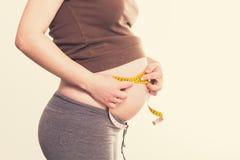 Η νέα έγκυος γυναίκα μετρά την κοιλιά της Στοκ φωτογραφίες με δικαίωμα ελεύθερης χρήσης
