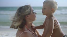 Η νέα έγκυος μητέρα κάθεται με το γιο της στην άμμο στην παραλία που φιλά και που έχει τη διασκέδαση το καλοκαίρι 4k απόθεμα βίντεο