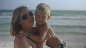 Η νέα έγκυος μητέρα κάθεται με το γιο της στην άμμο στην παραλία που φιλά και που έχει τη διασκέδαση το καλοκαίρι 4k φιλμ μικρού μήκους