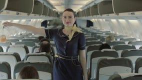 Η νέα αεροσυνοδός δίνει τις οδηγίες για τις μάσκες οξυγόνου φιλμ μικρού μήκους
