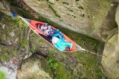 Η νέα ανάγνωση γυναικών κρατά χαλαρώνοντας στην αιώρα κοντά στον απότομο βράχο Στοκ Εικόνα