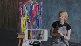 Η νέα αρκετά γυναίκα ζωγράφος blogger επικοινωνεί με τους οπαδούς της στον ατμοσφαιρικό εργασιακό χώρο τέχνης Οπτική επίδειξη απόθεμα βίντεο