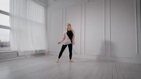 Η νέα αρκετά ξανθή γυναίκα προετοιμάζει την απόδοση χορού της στην άσπρη χορεύοντας αίθουσα, το άλμα και την περιστροφή απόθεμα βίντεο