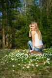 Η νέα αρκετά ξανθή γυναίκα σε ένα λιβάδι ανθίζει Στοκ Εικόνα