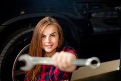Η νέα αρκετά προκλητική γυναίκα brunette στο ελεγχμένο πουκάμισο παρουσιάζει γαλλικό κλειδί Μακροεντολή θαμπάδων Στοκ Φωτογραφίες