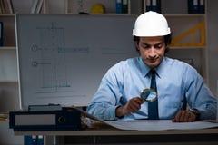 Η νέα αρσενική νύχτα εργασίας αρχιτεκτόνων στο γραφείο στοκ εικόνες