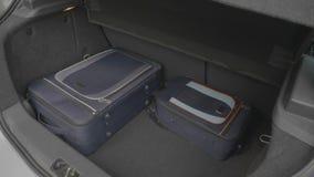 Η νέα αρσενική ορντινάντσα επιχειρηματιών οργανώνει τις βαλίτσες του μέσα στο αυτοκίνητο κορμών για ένα επαγγελματικό ταξίδι - απόθεμα βίντεο