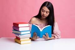Η νέα ασιατική γυναίκα διάβασε ένα βιβλίο με τα βιβλία στον πίνακα στοκ εικόνα με δικαίωμα ελεύθερης χρήσης