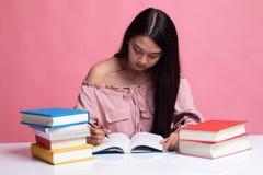 Η νέα ασιατική γυναίκα διάβασε ένα βιβλίο με τα βιβλία στον πίνακα στοκ εικόνες
