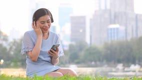 Η νέα ασιατική γυναίκα είναι απολαμβάνεται liftstyle με το άκουσμα στη μουσική με το ασύρματο ακουστικό απόθεμα βίντεο