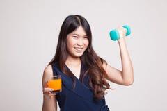 Η νέα ασιατική γυναίκα με τον αλτήρα πίνει το χυμό από πορτοκάλι Στοκ Εικόνες
