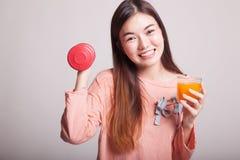 Η νέα ασιατική γυναίκα με τον αλτήρα πίνει το χυμό από πορτοκάλι Στοκ Φωτογραφία