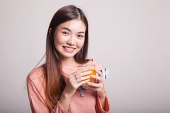 Η νέα ασιατική γυναίκα πίνει το χυμό από πορτοκάλι Στοκ φωτογραφία με δικαίωμα ελεύθερης χρήσης
