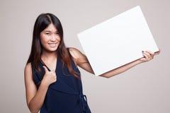 Η νέα ασιατική γυναίκα παρουσιάζει αντίχειρες με το άσπρο κενό σημάδι Στοκ εικόνα με δικαίωμα ελεύθερης χρήσης