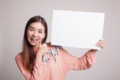 Η νέα ασιατική γυναίκα παρουσιάζει αντίχειρες με το άσπρο κενό σημάδι Στοκ Εικόνα