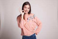Η νέα ασιατική γυναίκα παρουσιάζει ΕΝΤΑΞΕΙ σημάδι Στοκ Φωτογραφία