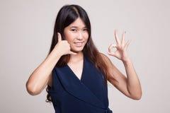 Η νέα ασιατική γυναίκα παρουσιάζει με την τηλεφωνική χειρονομία και το ΕΝΤΑΞΕΙ σημάδι Στοκ Εικόνα