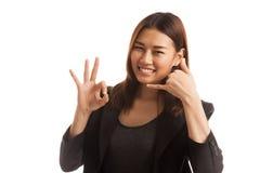 Η νέα ασιατική γυναίκα παρουσιάζει με την τηλεφωνική χειρονομία και το ΕΝΤΑΞΕΙ σημάδι Στοκ εικόνα με δικαίωμα ελεύθερης χρήσης