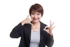 Η νέα ασιατική γυναίκα παρουσιάζει με την τηλεφωνική χειρονομία και το ΕΝΤΑΞΕΙ σημάδι Στοκ φωτογραφίες με δικαίωμα ελεύθερης χρήσης