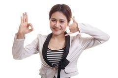 Η νέα ασιατική γυναίκα παρουσιάζει με την τηλεφωνική χειρονομία και το ΕΝΤΑΞΕΙ σημάδι Στοκ φωτογραφία με δικαίωμα ελεύθερης χρήσης