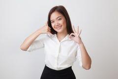 Η νέα ασιατική γυναίκα παρουσιάζει με την τηλεφωνική χειρονομία και το ΕΝΤΑΞΕΙ σημάδι Στοκ Εικόνες