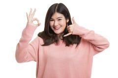 Η νέα ασιατική γυναίκα παρουσιάζει με την τηλεφωνική χειρονομία και το ΕΝΤΑΞΕΙ σημάδι Στοκ εικόνες με δικαίωμα ελεύθερης χρήσης