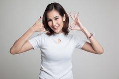 Η νέα ασιατική γυναίκα παρουσιάζει με την τηλεφωνική χειρονομία και το ΕΝΤΑΞΕΙ σημάδι Στοκ Φωτογραφίες