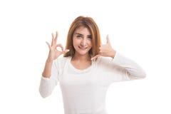 Η νέα ασιατική γυναίκα παρουσιάζει με την τηλεφωνική χειρονομία και το ΕΝΤΑΞΕΙ σημάδι Στοκ Φωτογραφία