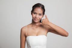 Η νέα ασιατική γυναίκα παρουσιάζει με την τηλεφωνική χειρονομία Στοκ Εικόνες