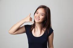 Η νέα ασιατική γυναίκα παρουσιάζει με την τηλεφωνική χειρονομία Στοκ Εικόνα