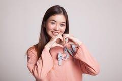 Η νέα ασιατική γυναίκα παρουσιάζει σημάδι χεριών καρδιών Στοκ Εικόνα