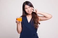 Η νέα ασιατική γυναίκα παρουσιάζει το σημάδι ότι νίκης πίνει το χυμό από πορτοκάλι Στοκ Φωτογραφία