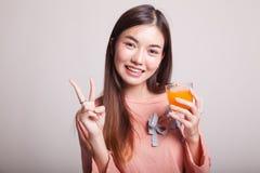 Η νέα ασιατική γυναίκα παρουσιάζει το σημάδι ότι νίκης πίνει το χυμό από πορτοκάλι Στοκ Εικόνα