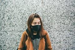 Η νέα ασιατική γυναίκα που φορά μια μαύρη στοματική μάσκα ως την πάσχει από την αυστηρή ατμοσφαιρική ρύπανση στοκ εικόνα