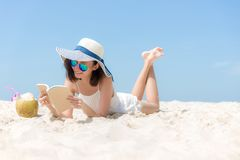Η νέα ασιατική γυναίκα τρόπου ζωής χαλαρώνει και ανάγνωση ένα βιβλίο στην όμορφη παραλία στο καλοκαίρι διακοπών, στοκ φωτογραφία