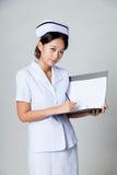Η νέα ασιατική εργασία νοσοκόμων για έναν φάκελλο εξετάζει τη κάμερα Στοκ φωτογραφία με δικαίωμα ελεύθερης χρήσης