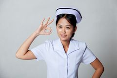 Η νέα ασιατική νοσοκόμα παρουσιάζει ΕΝΤΑΞΕΙ σημάδι στοκ φωτογραφία