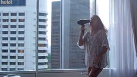 Η νέα αστεία χαρούμενη γυναίκα στις πυτζάμες που ξεραίνουν τους χορούς τρίχας τραγουδά τους γιους από το πανοραμικό παράθυρο στο  φιλμ μικρού μήκους