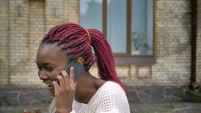 Η νέα αφρικανική όμορφη μετάβαση σπουδαστών μακρυά από πανεπιστημιακό και η ομιλία στο τηλέφωνο, γυναίκα με το ροζ φοβούνται στο  φιλμ μικρού μήκους