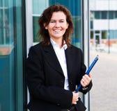 Η νέα βέβαια επιχειρηματίας με το φάκελλο κοντά στο γραφείο χτίζει Στοκ εικόνες με δικαίωμα ελεύθερης χρήσης