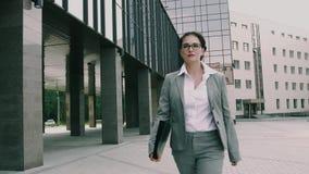 Η νέα βέβαια επιχειρησιακή γυναίκα που κρατά μια περίπτωση εγγράφων περπατά στο γραφείο φιλμ μικρού μήκους