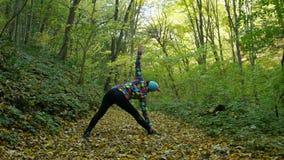 Η νέα γιόγκα άσκησης γυναικών το φθινόπωρο χρωμάτισε το δάσος ενώ τα κίτρινα φύλλα πέφτουν γύρω από την φιλμ μικρού μήκους