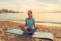 Γυναικών θέτει μέσα του λωτού στην παραλία στοκ εικόνα